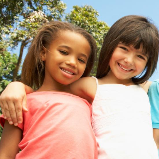 hymyilevät lapset rivissä ulkona