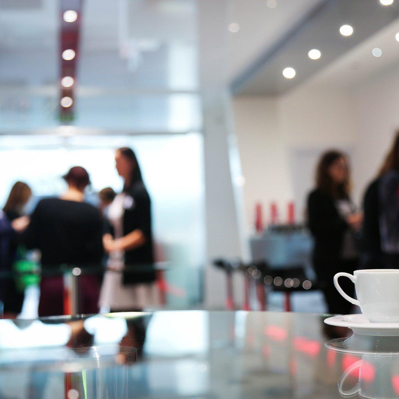 Ihmisiä juttelee keskenään taustalla, etualalla valkoinen kahvikuppi pöydällä