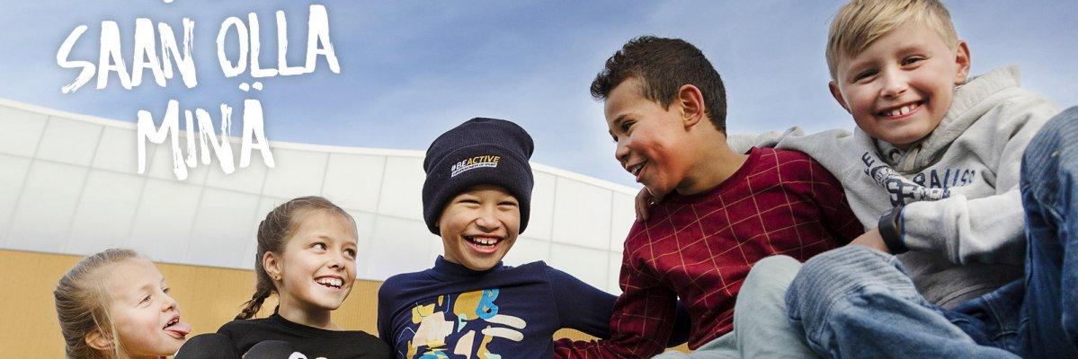 Nauravat lapset istuvat yhdessä.