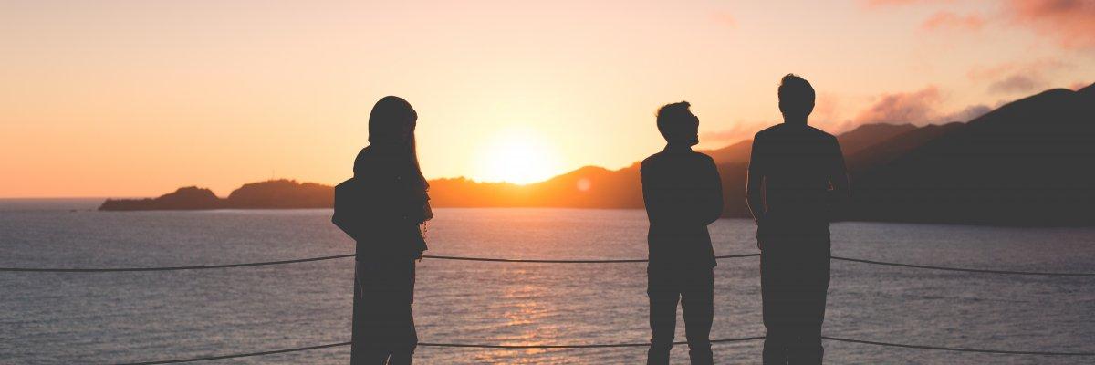 Kolme hahmoa seisovat katsellen edessä näkyvää merta jonka takaa pilkistää puoliksi laskenut aurinko