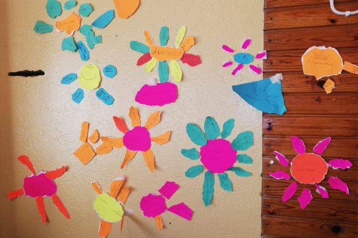 seinällä paperikukkasia joissa leiriosallistujien toiveita eri kielillä kirjoitettuna