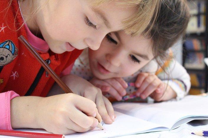 Kaksi lasta kirjoittamassa paperille.