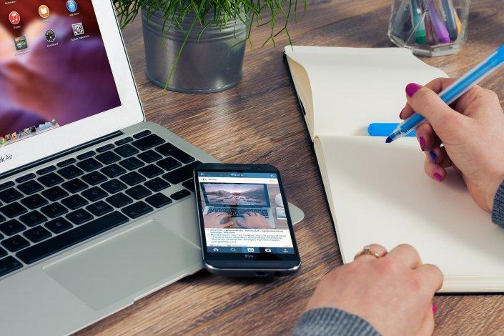 Henkilö tekemässä muistiinpanoja lehtiöön vieressään tietokone ja puhelin