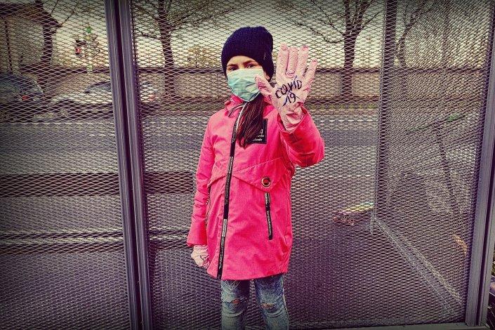Lapsi seisoo käsi ilmaan kohotettuna koronamaski kasvoillaan.